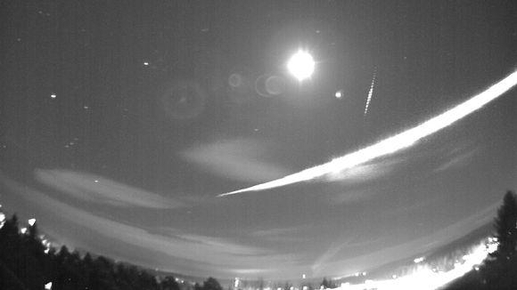 Taivaankannen yli ulottuva valojuova kuun vieressä.
