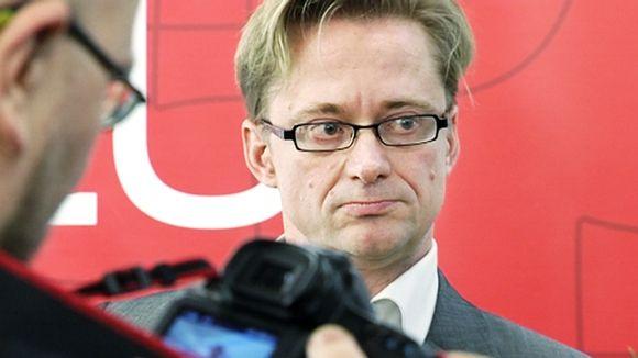 Video: Vakavailmeinen Mikael Jungner, etualalla valokuvaaja tutkii kameraansa.