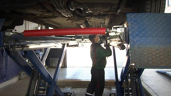 Katsastusmies tutkii autoa katsastusasemalla.