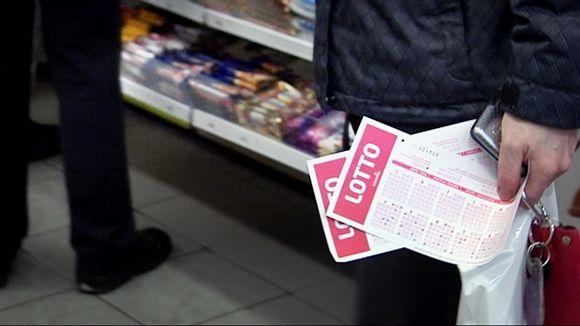 Lottoaja jonottaa kioskilla lottokupongit kädessään.