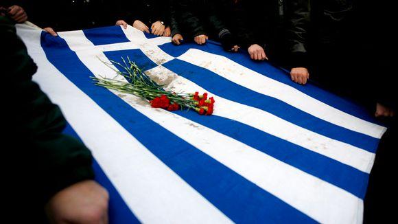 Video: Mielenosoittajat kantavat tuhriintunutta Kreikan lippua, jonka päällä on punaisia neilikoita.