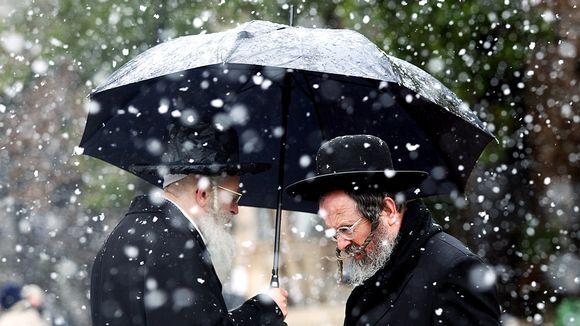 Kaksi parrakasta juutalaismiestä sateenvarjon alla lumisateessa.