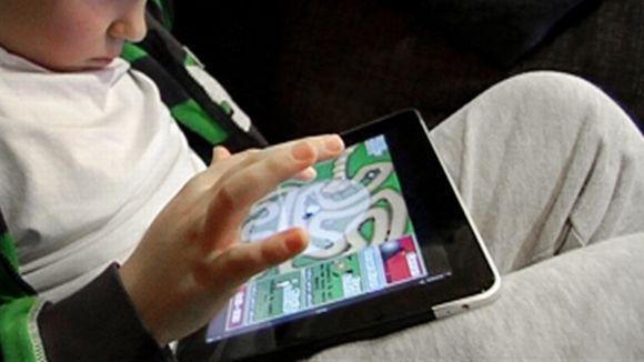 Lapsi pelaa nettipeliä tablet-tietokoneella.