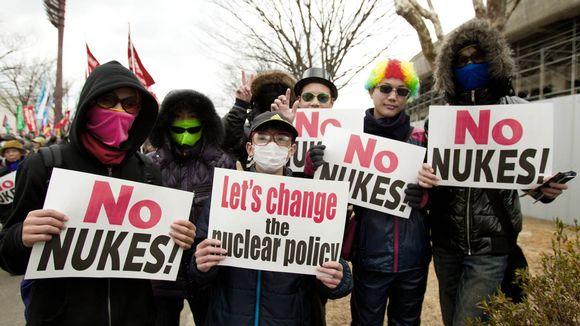 Hengityssuojaimin varustautuneet mielenosoittajat No-nukes-kylttiensä kanssa.