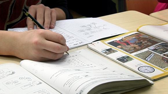 Oppilas kirjoittaa ruotsin kielen oppikirjaan.