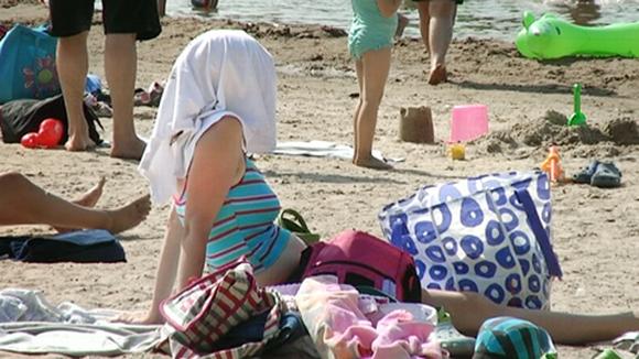 Video: Päänsä pyyhkeellä auringon paahteelta suojannut nainen istuu uimarannalla.