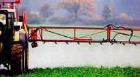 Maanviljelijä suihkuttaa pellolle hyönteistorjunta-ainetta.