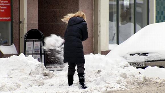 Nainen lapioi lunta pois auton edestä Helsingissä.