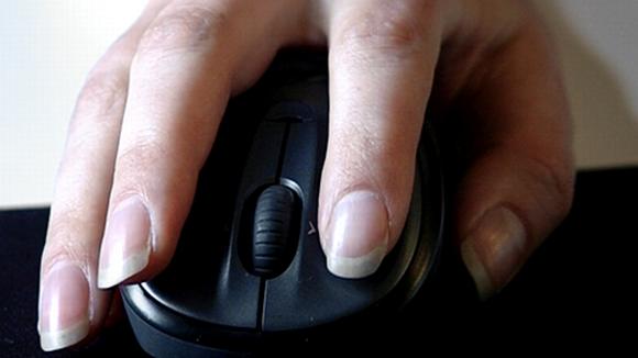 Naisen käsi tietokoneen hiirellä.