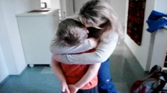 Äiti halaa poikaansa kotonaan.