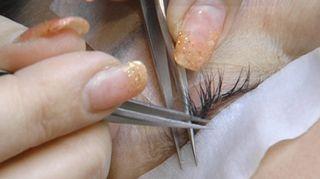 Kosmetologi asettelee irtoripsiä asiakkaalleen.
