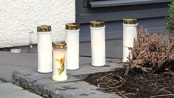 Kynttilöitä maassa talon edessä.