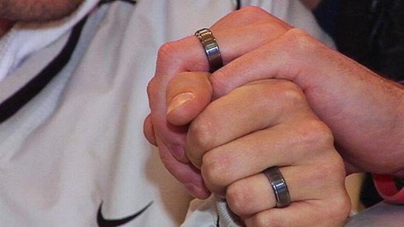 Kahden miehen kädet yhdessä, molempien nimettömissä sormus.
