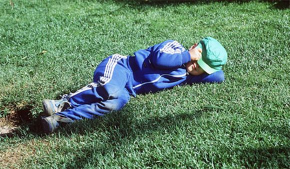 Poika nukkuu nurmikolla