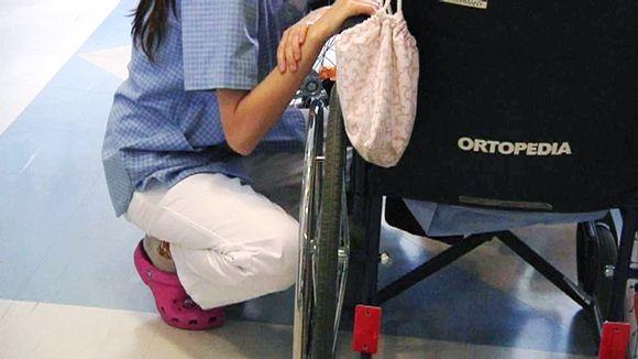 Hoitaja kyykyssä pyörätuolin vieressä.