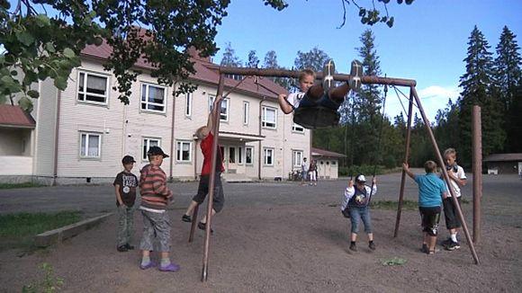 Kojon koulu ja pihalla leikkiviä lapsia
