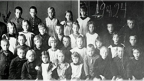 Tyttöjä ja poikia vakana luokkakuvassa liitutaulun edessä