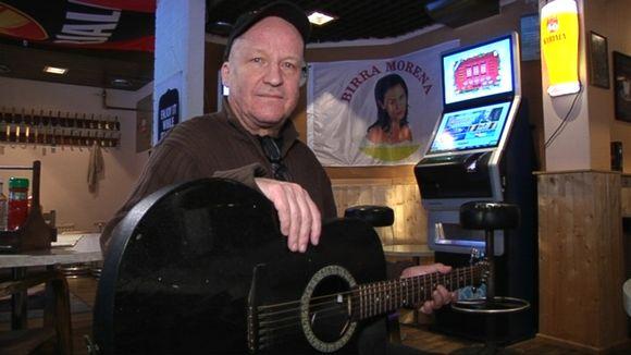Video: Mies katsoo kameraan kitara kädessään