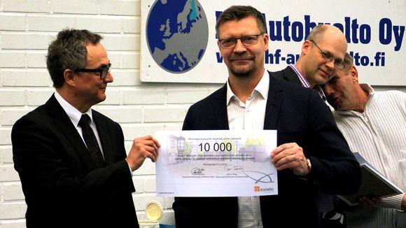 Mies ojentaa 10 000 euron shekin Jukka Jaloselle