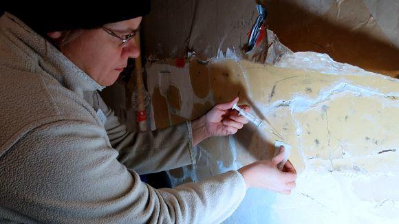Nainen injektioruisku kädessä työntää neulaa seinänrakoon.