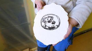 Naisella palanen rappausta käsissään, johon on piirrettynä koiramainen hahmo.