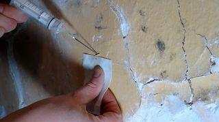 Injektioruisku tunkeutuu vanhaan likaiseen seinäpintaan