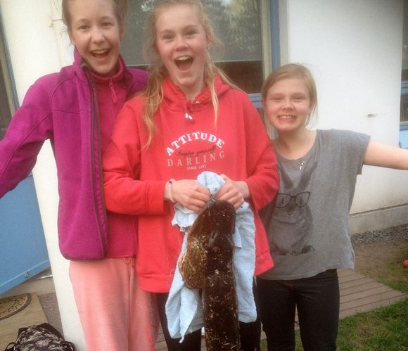 Kolme nuorta naista nauravat kameralle ja yksi heistä kannattelee jättihaukea
