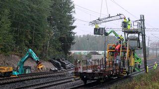 Miehiä telineillä junaradalla
