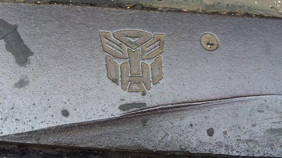 Kuva raitiovaunun kiskoihin kaiverretusta transformers -logosta