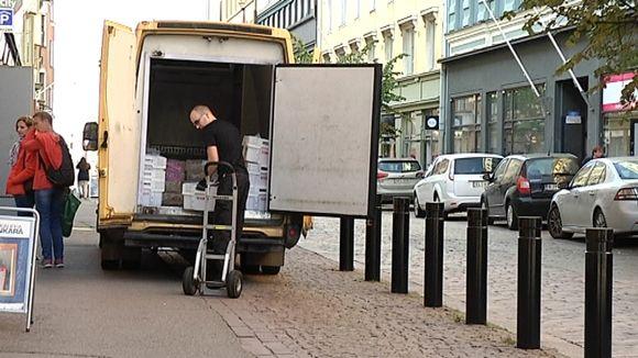 Mies tyhjentää pakettiautoa