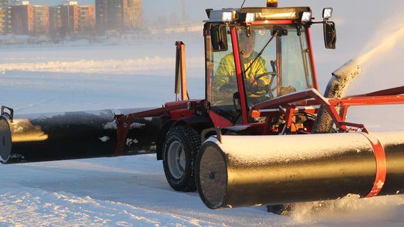 Ponttoonitraktori linkoaa lunta.