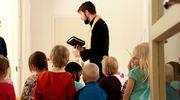 Pastori Mikko Sidoroff seisoo raamattu kädessään lasten edessä.