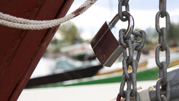 Riippulukko roikkuu ketjuissa veneen kokassa.
