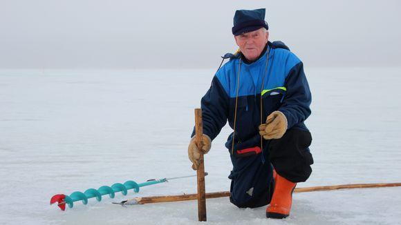 Raimo Virkkunen mittaa jään paksuutta Pyhäselällä.