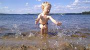 Pikkupoika pärskii vettä uimarannalla.