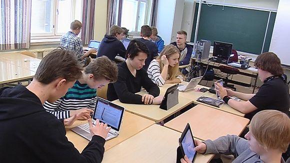 Lukiolaiset tekevät ryhmätyötä tablettien ja tietokoneiden ääressä.