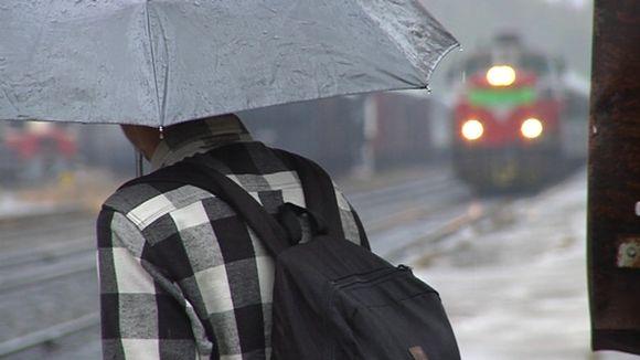 Nuori mies odottaa asemalle saapuvaa junaa.