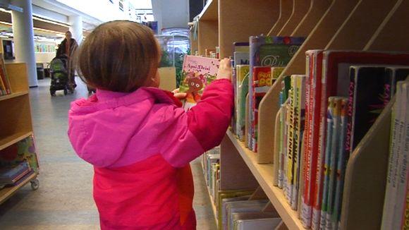 Lapsi etsii kirjaston hyllystä luettavaa.