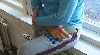 Anonyymi turvapaikanhakija nojaa ikkunalautaan kännykkä kädessään.