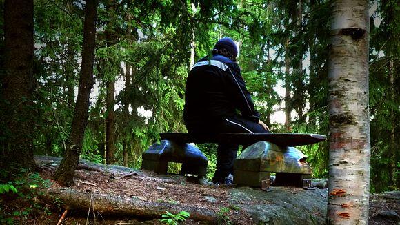 Mies istuu penkillä metsässä.