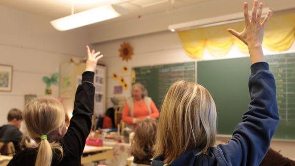 Oppilaat viittaavat luokassa.