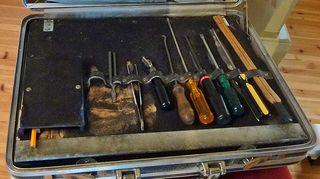 Pianonvirittäjän työkalusalkussa on meisseleitä, koukkuja sekä pianonkielet erottavia läpysköjä.