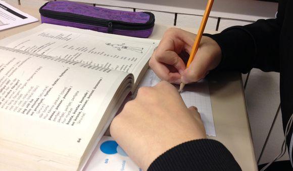 Oppilas kirjoittaa koulutehtäviä.