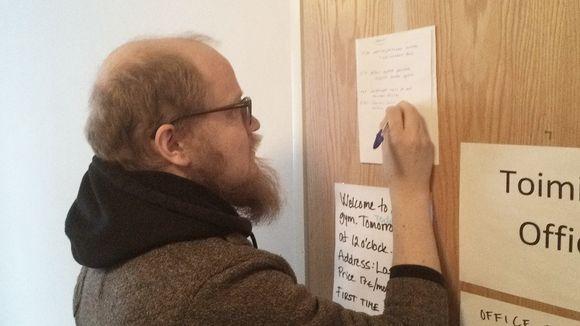 Tommi Rajala kirjoittaa viestiä seinää vasten