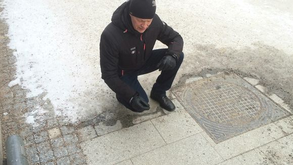 Mies tarkastelee katukiveyksen kuntoa.
