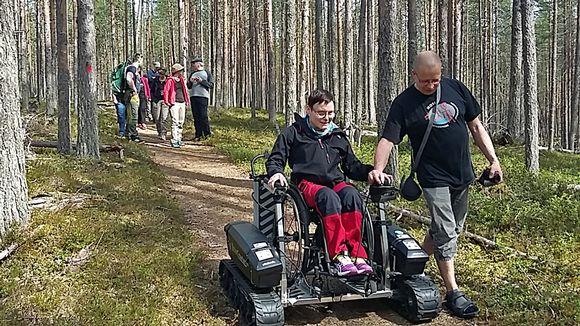 Nainen pyörätuolissa kulkee luonnossa telavaunun avulla