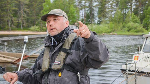 Lasse Aarnipuro osoittaa sormella Oulujärvelle.