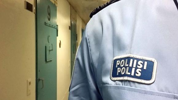 Poliisinmerkki virkapaidassa ja taustalla useita putkanovia.