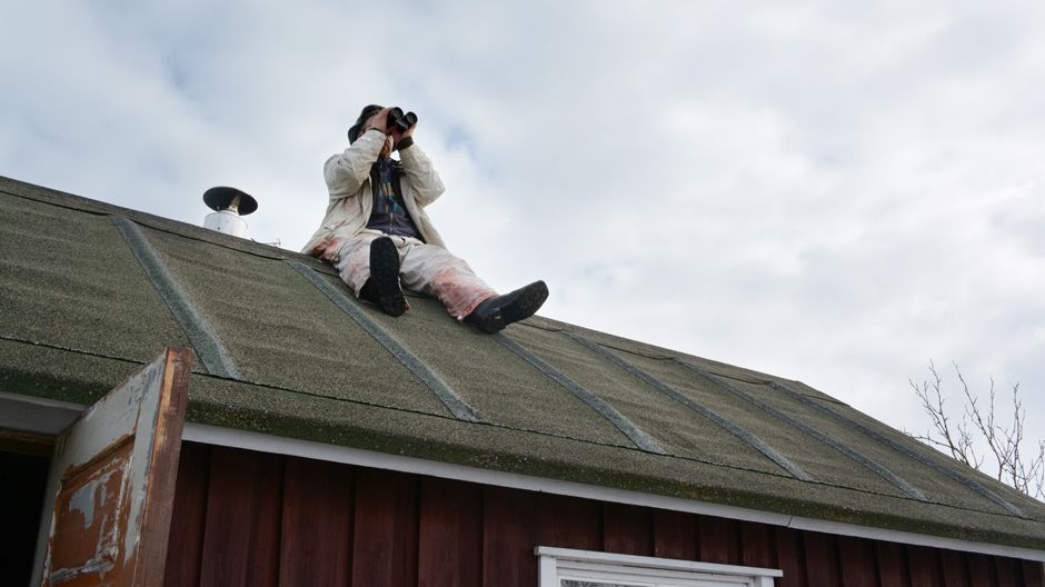 Hylkeenpyytäjä Sauli Kehus tähystää katolla.