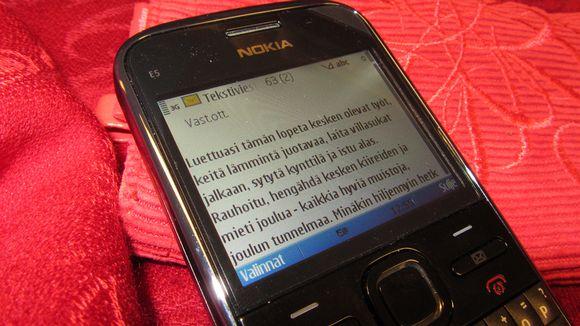 Kuvassa kännykkä, jonka näytöllä näkyy jouluinen tekstiviesti